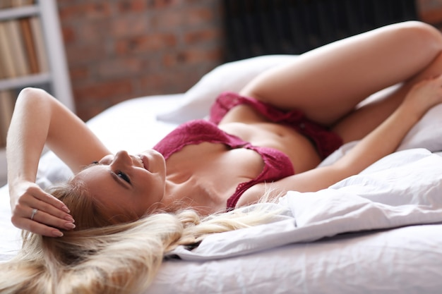 Beautiful woman wearing sexy red lingerie on the bed