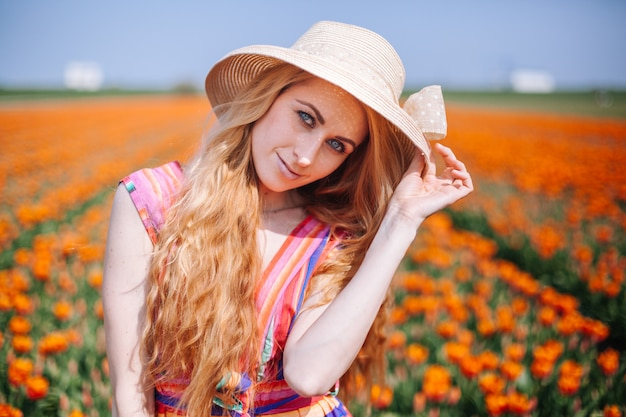 Beautiful woman wearing in striped dress and straw hat standing on colorful flower tulip field