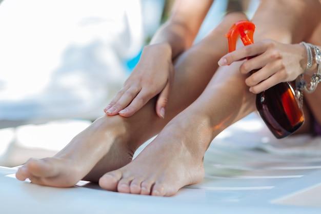 일광욕하기 전에 태양 보호 크림을 씌우는 세련된 팔찌를 착용하는 아름다운 여인