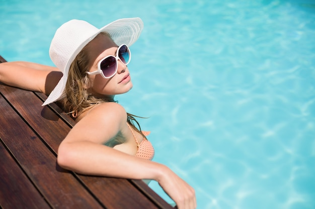 Beautiful woman wearing sunglasses and straw hat leaning on wooden deck by poolside