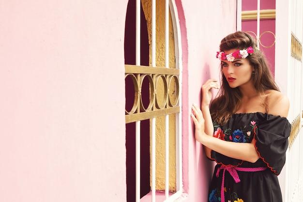伝統的なメキシコのドレスを着ている美しい女性がピンクの壁の横にポーズをとってください。