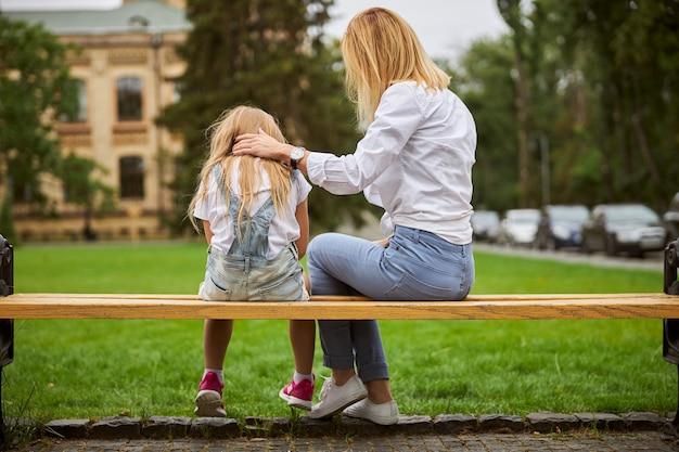 흰 블라우스와 청바지를 입고 아름다운 여인이 그녀의 딸을 돌보고주의를 기울입니다. 프리미엄 사진