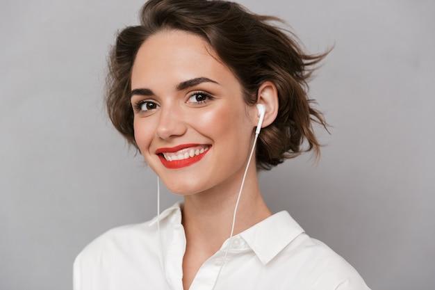 笑顔、灰色の壁に隔離の白いイヤホンを身に着けている美しい女性
