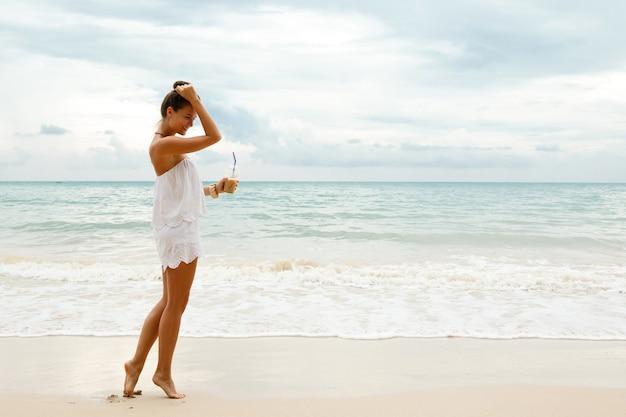 아이스 커피 한 잔과 함께 해변에서 흰색 죄수 복 도보를 입고 아름 다운 여자
