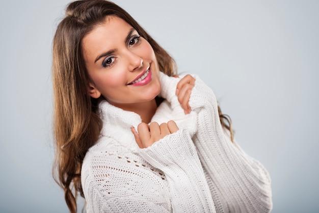 白い暖かいセーターを着ている美しい女性