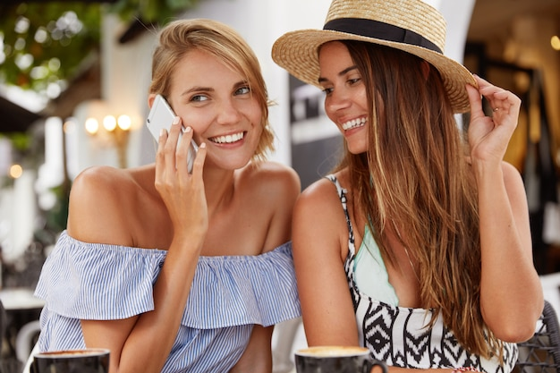 美しい女性はファッショナブルなブラウスを着ており、芳香族コーヒーを飲みながらテラスカフェで彼女のガールフレンドの近くに座っている間、誰かと電話で会話しています。人、レジャー、テクノロジー、ライフスタイル。