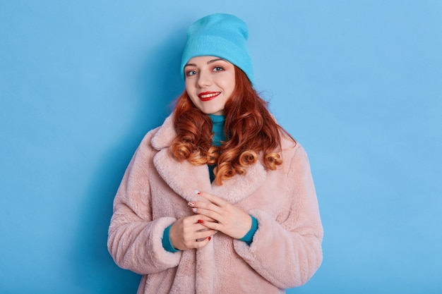 Beautiful woman wears pink fur coat and blue cap, smiles toothily