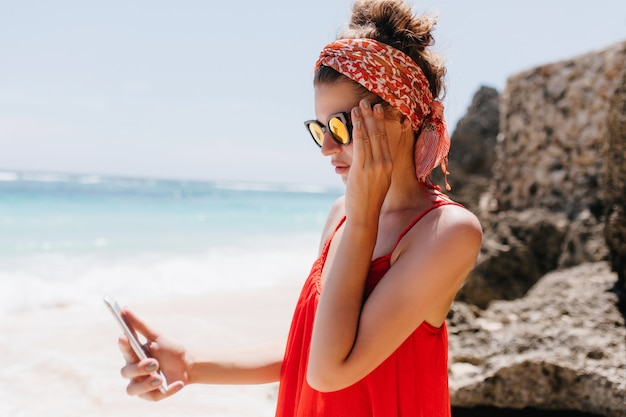 Beautiful woman wears sparkle sunglasses standing near rocks with smartphone. elegant tanned girl in red dress looking at phone screen while resting at beach.