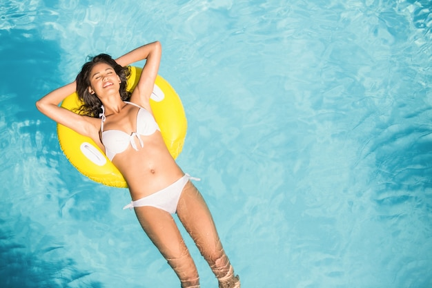 Beautiful woman in white bikini floating on inflatable tube in swimming pool