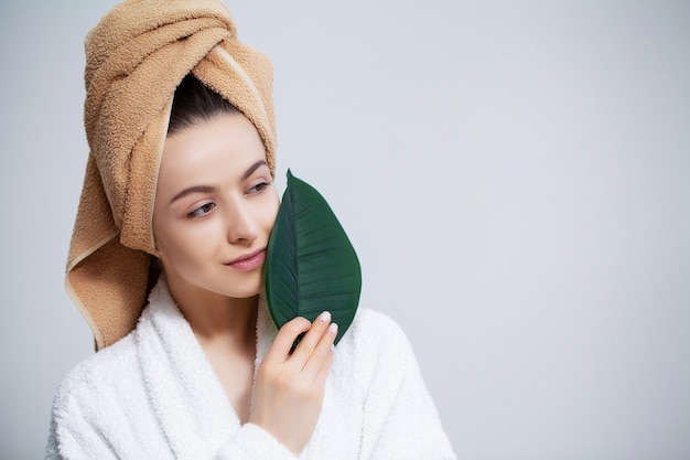 Beautiful woman in a white coat with a towel on her head and clear skin holds a green leaf