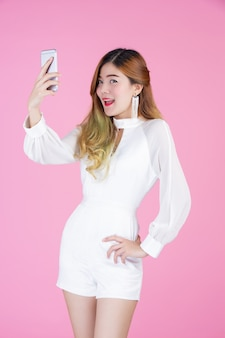 Beautiful woman, white dress showing the phone and the mood of the face