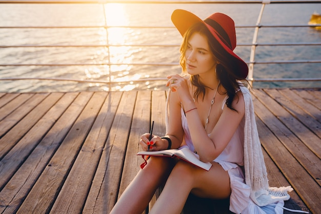 Beautiful woman in white dress sitting by the sea on sunrise thinking and making notes in diary book
