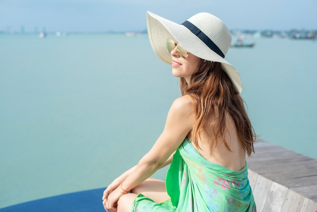 Beautiful woman in white hat is sitting on the hotel with the beach