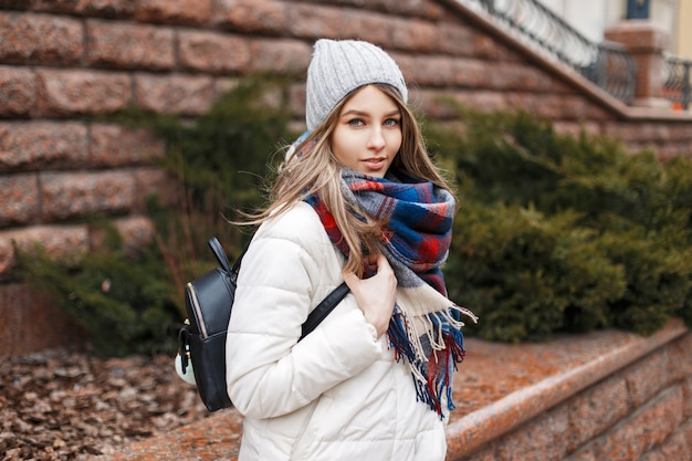 Beautiful woman in a white jacket, hat and bright scarf near the wall