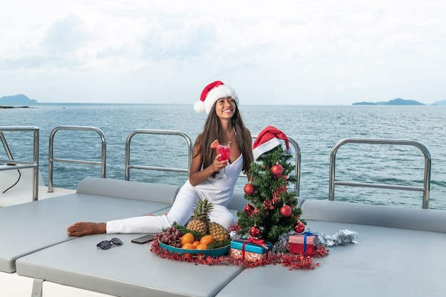 Beautiful woman in a white jumpsuit and hat of santa claus on the yacht.