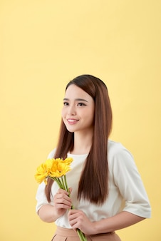 Beautiful woman in the white shirt with flowers gerbera in hands on a yellow background. she smiles and laughs