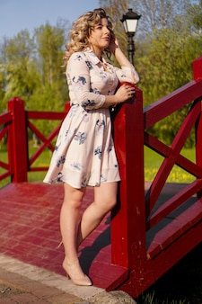 Beautiful woman in a white summer dress and a straw hat stands on a birch bridge in the park