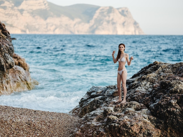 Beautiful woman in a white swimsuit stands on a high stone in nature and white foam ocean clear water. high quality photo