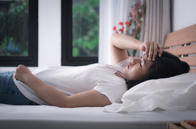 Beautiful  woman in white t-shirt and blue jean get headache and cold lying down in bed