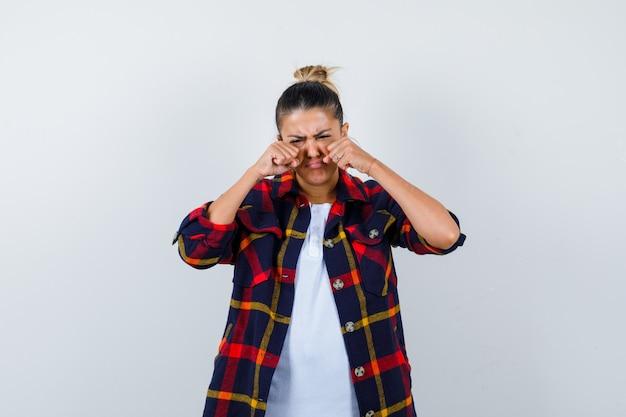 Bella donna in t-shirt bianca, camicia a quadri con pugni vicino agli occhi mentre piange e sembra triste, vista frontale.
