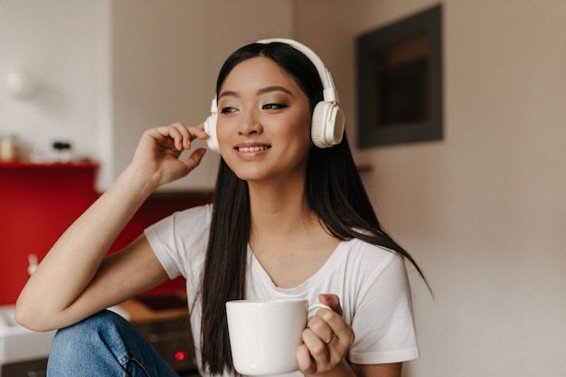 Beautiful woman in white t-shirt and headphones is listening to music over cup of tea