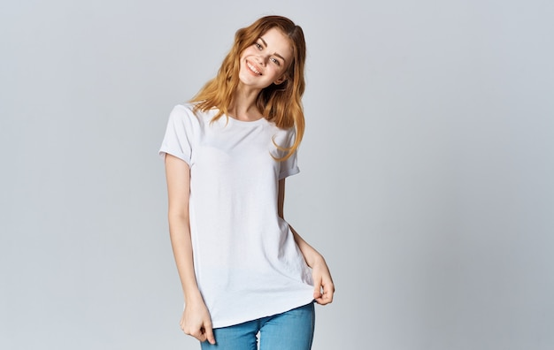 A beautiful woman in a white t-shirt and jeans smiles on a gray background and gestures with her hands.