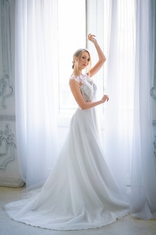 A beautiful woman in a white wedding dress with a beautiful make-up and hairstyle stands on the window