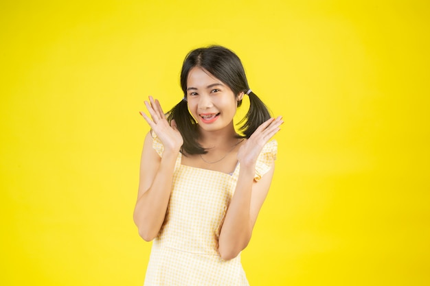 A beautiful woman who is happy showing various gestures on a yellow .