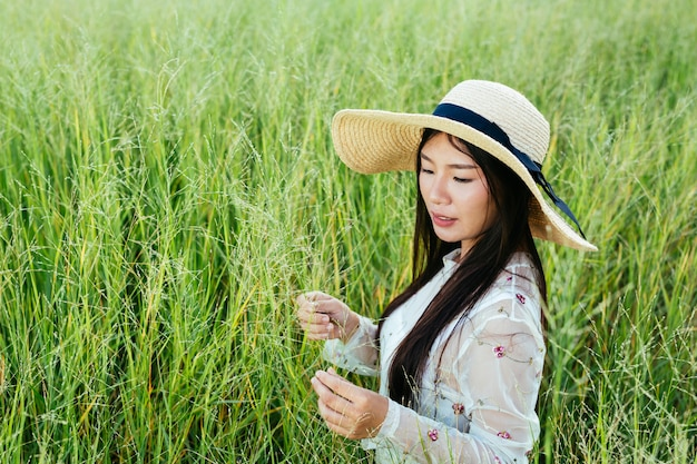 A beautiful woman who is sitting in the grassland happily.