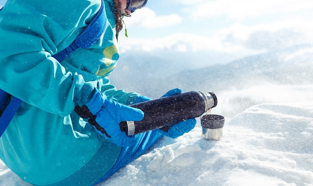 Beautiful woman in winter clothes drinking tea in the mountains. concept of travel, leisure, freedom, sport.