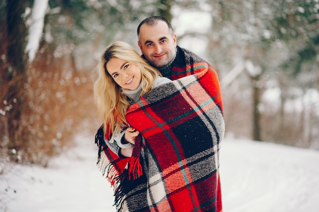 Beautiful woman in a winter park with her husband