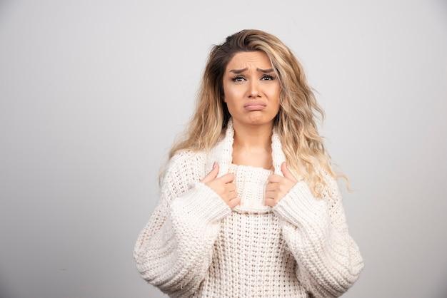 Beautiful woman in winter sweater looking sad.