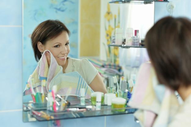 美しい女性がバスルームでタオルで顔を拭く