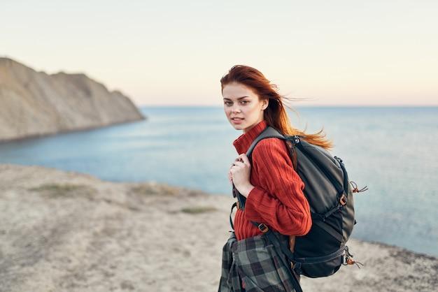 山の赤いセーターモデルの髪型海の海でバックパックを持つ美しい女性