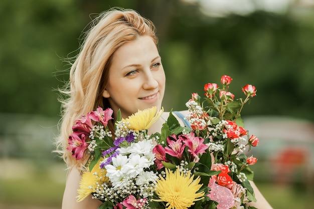 公園のぼやけた壁に花束を持つ美しい女性