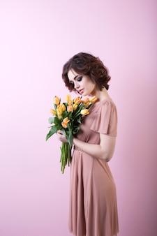 Красивая женщина с букетом цветов на розовом фоне.