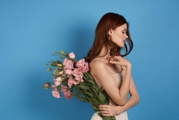 青色の背景の春モデルの肖像画にピンクの花の花束を持つ美しい女性