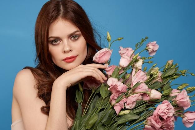 青色の背景の春モデルにピンクの花の花束を持つ美しい女性
