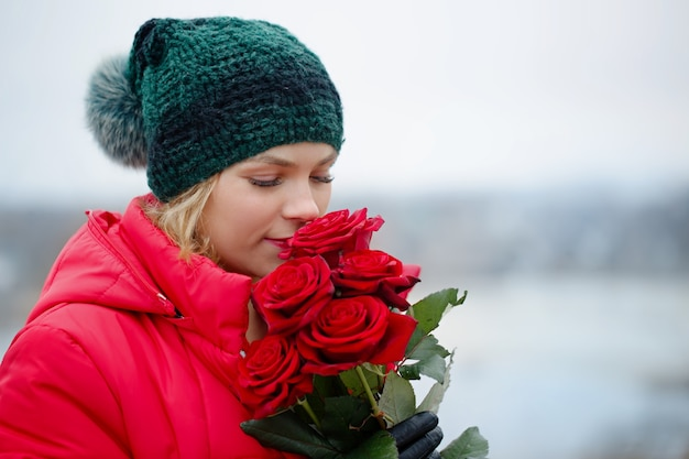그녀의 손에 빨간 장미 꽃다발과 함께 아름 다운 여자