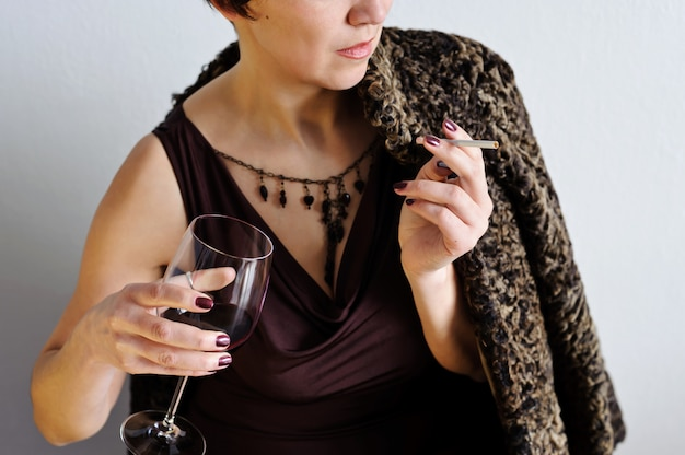 담배와 레드 와인 한 잔을 가진 아름 다운 여자