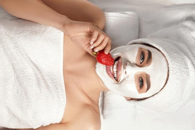 彼女の顔に粘土のマスクと手にイチゴを持つ美しい女性。スパ。フェイスピーリングマスク。スキンケア。