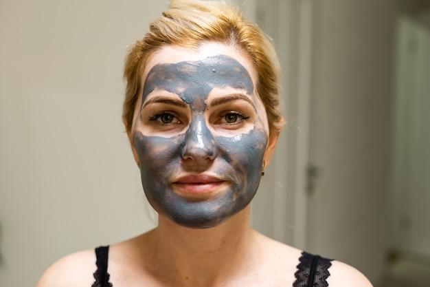 흰색 배경 위에 얼굴에 진흙이나 진흙 마스크를 쓴 아름다운 여성