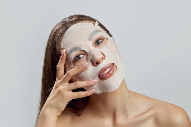 얼굴에 천 보습 마스크와 아름 다운 여자. 페이셜 및 스파 트리트먼트. 화장품 마스크.