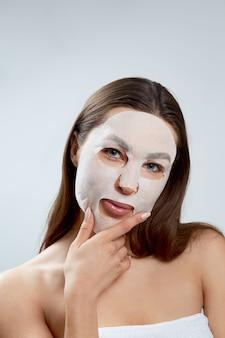 얼굴에 천 보습 마스크와 아름 다운 여자. 피부 관리 . 페이셜 및 스파 트리트먼트. 화장품 마스크.