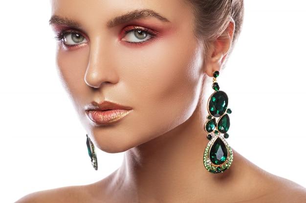 カラフルな化粧品で美しい女性は緑のエメラルドのイヤリングを着ています。