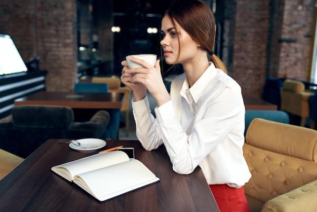 手にカップを持つ美しい女性は、カフェのテーブルに座って、レストランを予約します