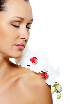彼女の肩に花を持つ美しい女性