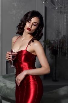 Красивая женщина с бокалом в руке в красном платье.