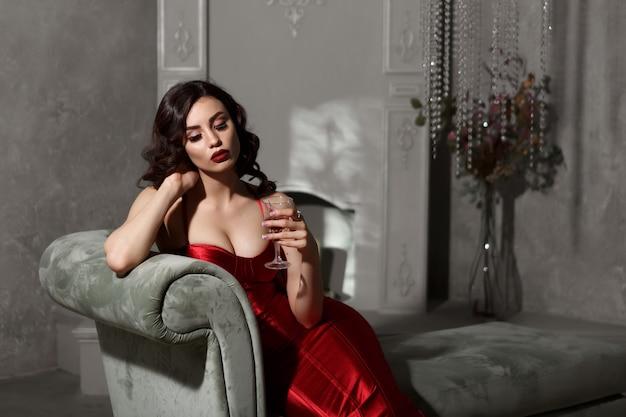 Красивая женщина с бокалом в руке, сидя на диване.