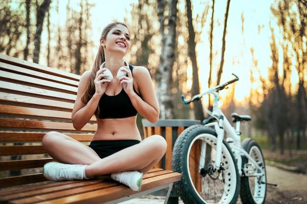 Красивая женщина с прической сидит и улыбается на скамейке возле велосипеда на закате в парке